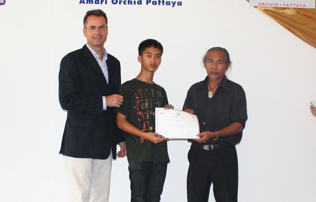 Amari's Residenzmanager Richard Margo, und Künstler Chanarong Kosolwat übergeben an Nattawut Chumanowat ( Mitte) von der Silapakorn Universität eine Urkunde.