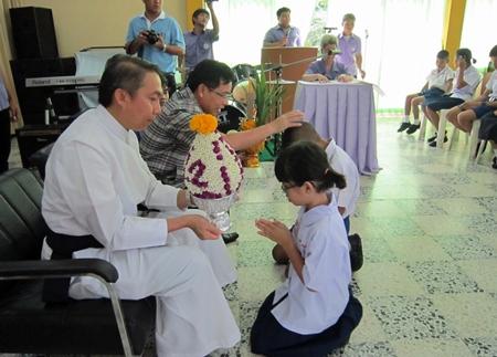 Kleine Schüler schenken ihren Wohltätern Priester Pattarapol Sriworakul (links), und Supamit Sirakantamakul Blumen, Kerzen und Räucherstäbchen.