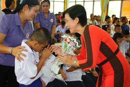 Rachada Chomjinda, Direktorin der HHN Stiftung Thailand (rechts), nimmt hand- gefertigte Blumensträuße entgegen.